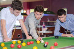 Trois hommes autour de table de billard Photo stock