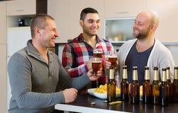 Trois hommes avec de la bière à la cuisine Photos stock