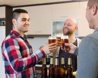 Trois hommes avec de la bière à la cuisine Image stock