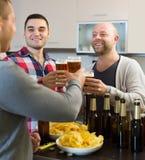 Trois hommes avec de la bière à la cuisine Photo libre de droits