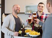 Trois hommes avec de la bière à la cuisine Image libre de droits