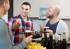 Trois hommes avec de la bière à la cuisine Images libres de droits