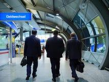 Trois hommes d'affaires à la station de train marchant vers la porte Photos libres de droits