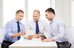Trois hommes d'affaires de sourire avec le PC de comprimé dans le bureau Photographie stock