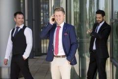 Trois hommes d'affaires de sourire se tenant dehors Photographie stock libre de droits