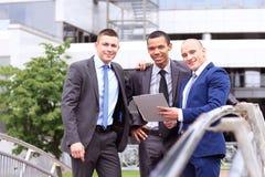 Trois hommes d'affaires discutant le document en dehors du bureau Photos stock