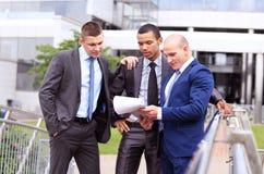 Trois hommes d'affaires discutant le document en dehors du bureau Photos libres de droits