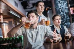 Trois hommes d'affaires réussis boivent de la bière et se réjouissent et crient à Photos stock