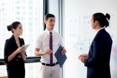 Trois hommes d'affaires se tenant dans le bureau moderne regardant le document de dossier et parlant dans le lieu de réunion Photographie stock libre de droits