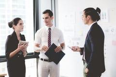 Trois hommes d'affaires se tenant dans le bureau moderne regardant le document de dossier Photo stock