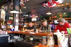 Trois hommes d'Alaska ayant une bière dans Haines Photos stock