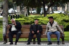 Trois hommes dans la conversation sur un banc à Bakou, Azerbaïdjan Photographie stock libre de droits