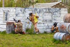 Trois hommes dans la situation dynamique avec le drapeau de paintball Images stock