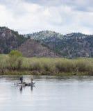 Trois hommes dans un bateau à rames Images stock