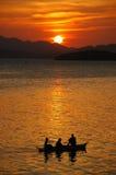 Trois hommes dans un bateau Photographie stock