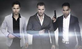 Trois hommes de mode tenant l'arme à feu photos libres de droits