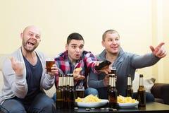 Trois hommes observant le football avec de la bière d'intérieur Photo stock