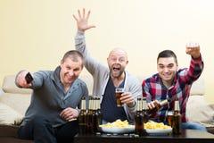 Trois hommes observant le football avec de la bière d'intérieur Photographie stock