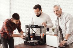 Trois hommes ont installé une imprimante 3d qui a réussi tout seul pour imprimer l'objet Un homme plus âgé avec un ordinateur por Photos libres de droits