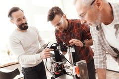 Trois hommes ont installé une imprimante 3d qui a réussi tout seul pour imprimer la forme Ils préparent l'imprimante pour lancer  Images libres de droits
