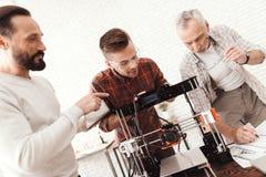 Trois hommes ont installé une imprimante 3d qui a réussi tout seul pour imprimer la forme Ils préparent l'imprimante pour lancer  Photos libres de droits