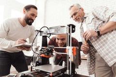 Trois hommes ont installé une imprimante 3d qui a réussi tout seul pour imprimer la forme Ils préparent pour lancer le dispositif Image libre de droits