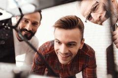 Trois hommes ont installé une imprimante 3d qui a réussi tout seul pour imprimer la forme Ils préparent pour lancer le dispositif Photographie stock libre de droits