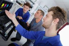 Trois hommes regardant des cartouches d'encre dans le photocopieur photographie stock libre de droits