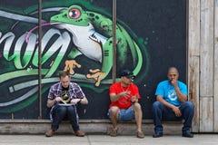 Trois hommes s'asseyant avec une grenouille Image libre de droits