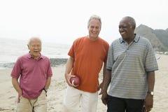 Trois hommes supérieurs marchant sur la plage photos stock