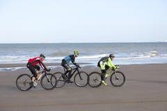 Trois hommes sur le vélo de montagne sur la plage avec le ciel bleu Photo stock