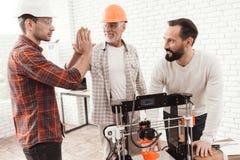 Trois hommes travaillent pour préparer imprimé sur une imprimante du modèle 3d Ils tiennent trois ensemble autour du printert 3d Image libre de droits