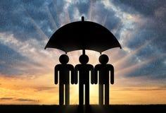 Trois icônes de petits hommes se tiennent sous le parapluie ensemble Photographie stock