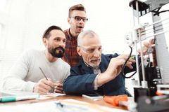 Trois ingénieurs impriment les détails sur l'imprimante 3d Un homme de personnes âgées commande le processus Deux autres suivent  Photos libres de droits