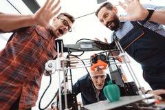 Trois ingénieurs sont enchantés pour voir comment l'imprimante 3d a imprimé un modèle de pomme Image stock