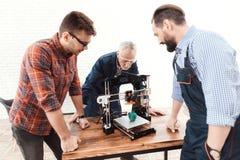 Trois ingénieurs sont enchantés pour voir comment l'imprimante 3d a imprimé un modèle de pomme Photo libre de droits