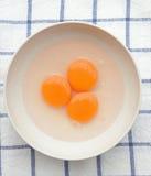 Trois jaunes d'oeuf jaunes dans la cuvette blanche (vue supérieure) Image libre de droits