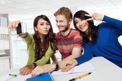 Trois jeunes adolescents prenant un autoportrait avec un téléphone Photos libres de droits