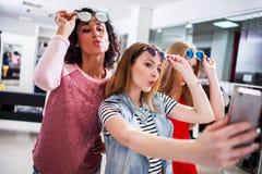 Trois jeunes amies élégantes soulevant les lunettes de soleil à la mode tout en prenant le selfie avec le smartphone dans le cent Images stock