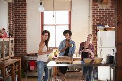 Trois jeunes amies adultes dans la cuisine regardent à l'appareil-photo Image stock