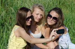 Trois jeunes amies heureuses faisant le selfie par le téléphone Photo stock