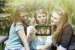 Trois jeunes amies heureuses faisant le selfie par le téléphone Images libres de droits