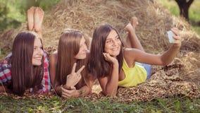 Trois jeunes amies heureuses faisant le selfie par le téléphone Photos stock