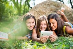 Trois jeunes amies heureuses faisant le selfie par le téléphone Photographie stock libre de droits