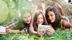 Trois jeunes amies heureuses faisant le selfie par le téléphone Photographie stock
