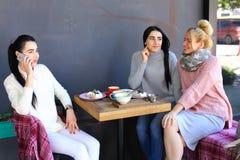 Trois jeunes amies magnifiques de fille vibrent, bavardant, sha Photo libre de droits
