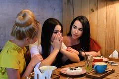 Trois jeunes amies mignonnes de fille vibrent, bavardant, secr de part Image stock