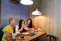 Trois jeunes amies mignonnes de fille vibrent, bavardant, secr de part Images stock