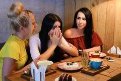 Trois jeunes amies mignonnes de fille vibrent, bavardant, secr de part Image libre de droits