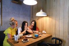 Trois jeunes amies mignonnes de fille vibrent, bavardant, secr de part Photos stock